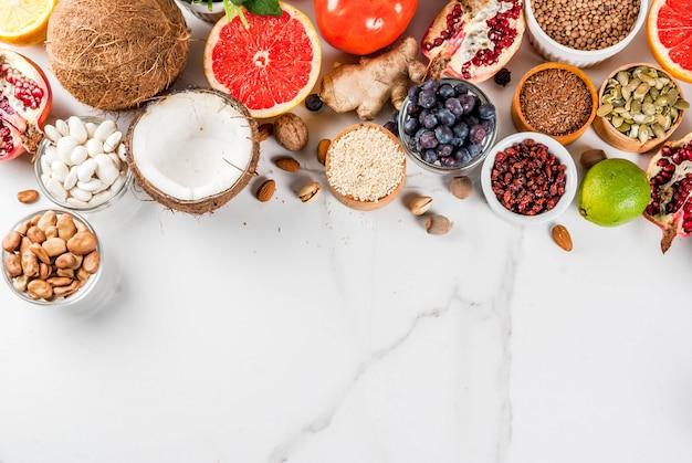 Satz organisches lebensmittel der gesunden diät, superfoods - bohnen, hülsenfrüchte, nüsse, samen, grüns, obst und gemüse weiß. ansicht von oben