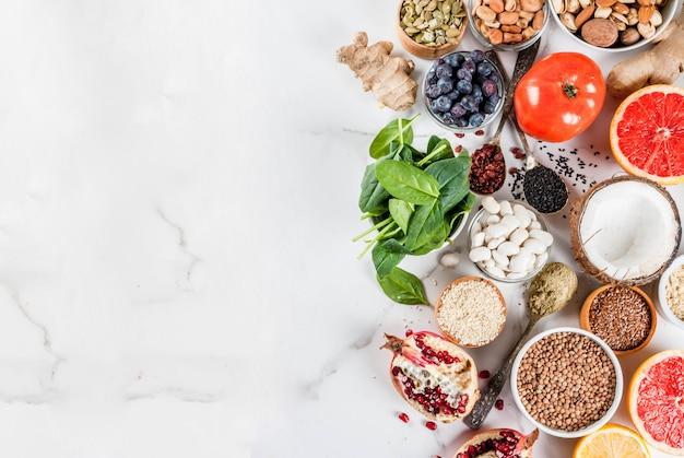 Satz organisches lebensmittel der gesunden diät, superfoods - bohnen, hülsenfrüchte, nüsse, samen, grüns, obst und gemüse weißer hintergrundkopienraum.