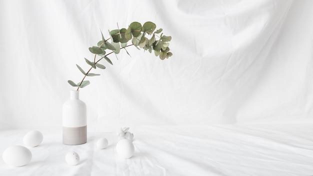 Satz ostereier nahe grünpflanzenniederlassung im vase