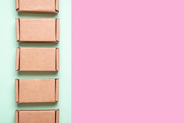 Satz pappkartons auf rosa, grünem hintergrund