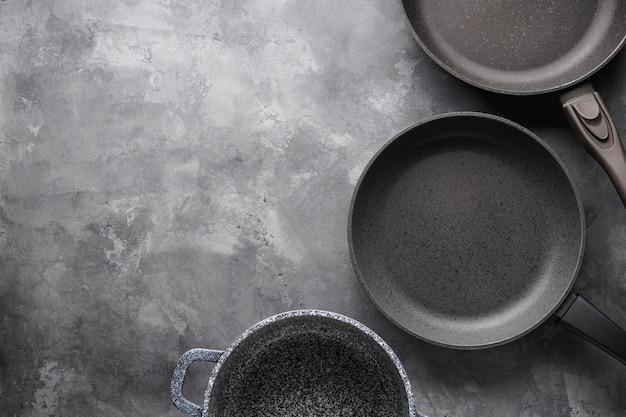Satz pfannen. verschiedene küchenutensilien auf grauem tisch, flach gelegt