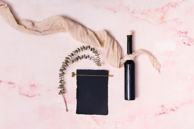 Satz pflanzenzweige und papier nahe gewebe und flasche