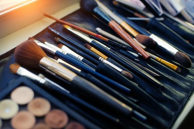 Satz pinsel für professionelles make-up im speziellen schwarzen fall, nahaufnahme. eine vielzahl von pinseln und applikatoren, visagistenwerkzeug.