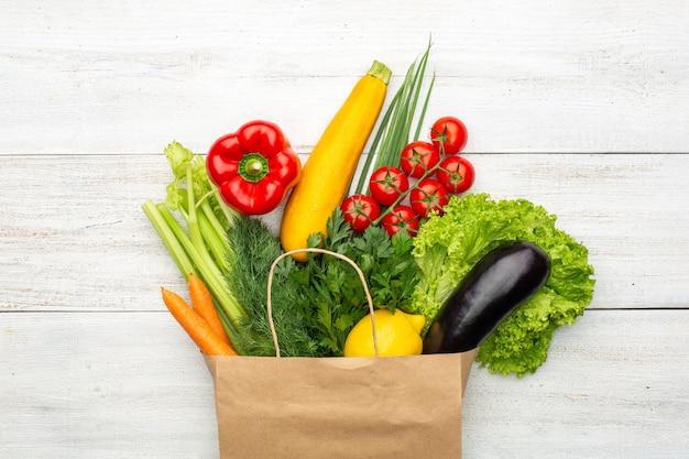 Satz produkte in einer papiertüte auf einem weißen hölzernen hintergrund auch im corel abgehobenen betrag. einkaufen in einem supermarkt oder markt. konzept: gesundes vegetarisches essen.