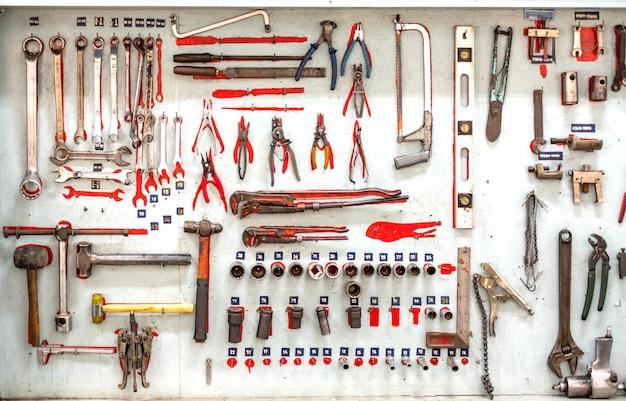 Satz professionelle mechanische werkzeuge, die an einer wand hängen