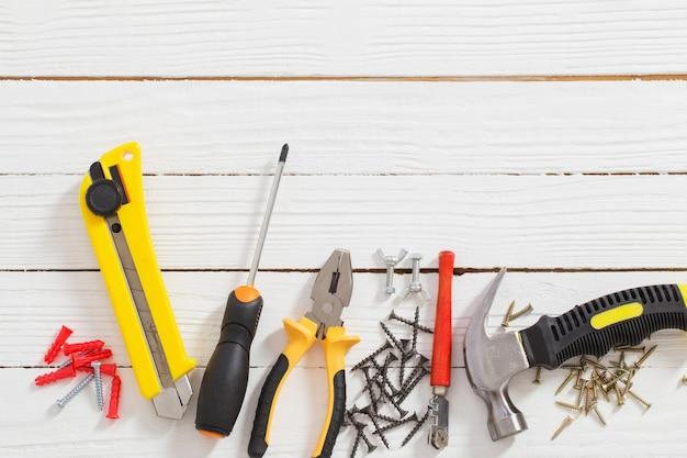 Satz reparaturwerkzeuge auf weißem hölzernem hintergrund