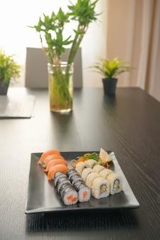 Satz rollen und sushi auf schwarzer rechteckiger platte auf schwarzer tabelle, anlagen auf hintergrund, selektiver fokus. japanisches essen thema