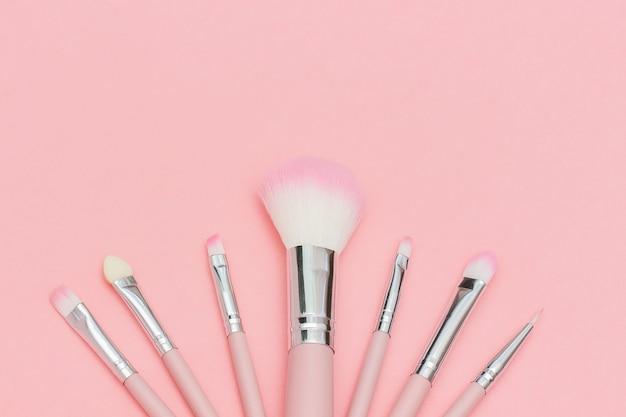 Satz rosa make-up-pinsel auf pastellrosa hintergrund