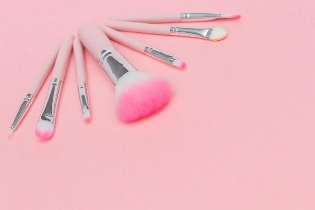 Satz rosa make-upbürsten auf pastellrosahintergrund