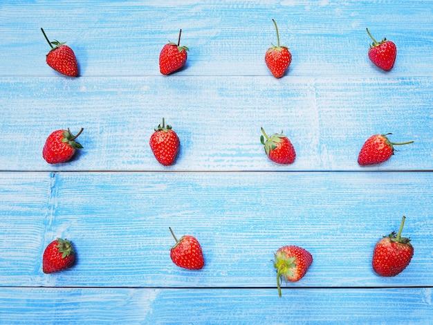 Satz rote erdbeeren auf blauem hölzernem hintergrund. saftige früchte.