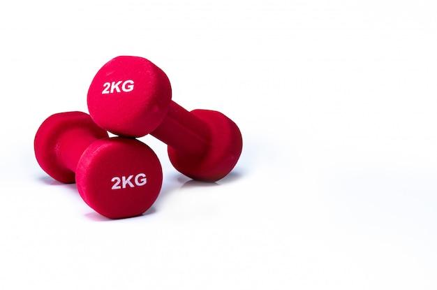 Satz rote hanteln lokalisiert auf weißer wand. ein paar rote neoprenhanteln. heim-fitnessgeräte für das training zu hause. krafttrainingsgeräte für arme, schultern, rücken und beine.