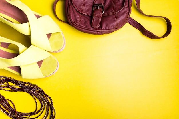 Satz sachen-zubehör der frau zur sommersaison. braune tasche gelbe plateausandalen, halskette. flache lage.