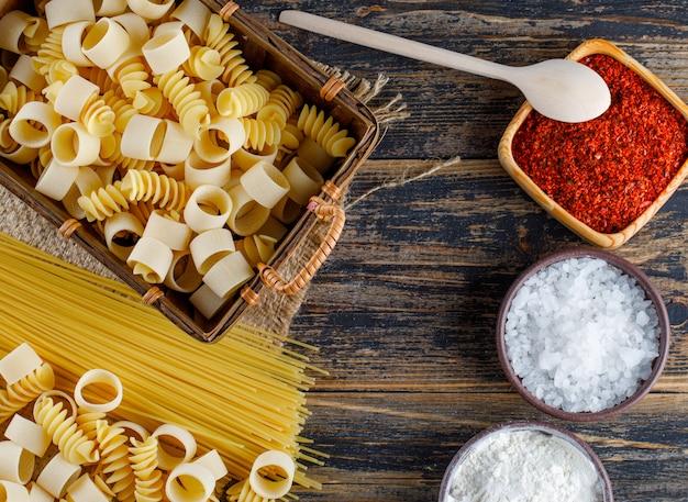 Satz salz, rote gewürze, spaghetti und makkaroni-nudeln auf einem hölzernen hintergrund. flach liegen.