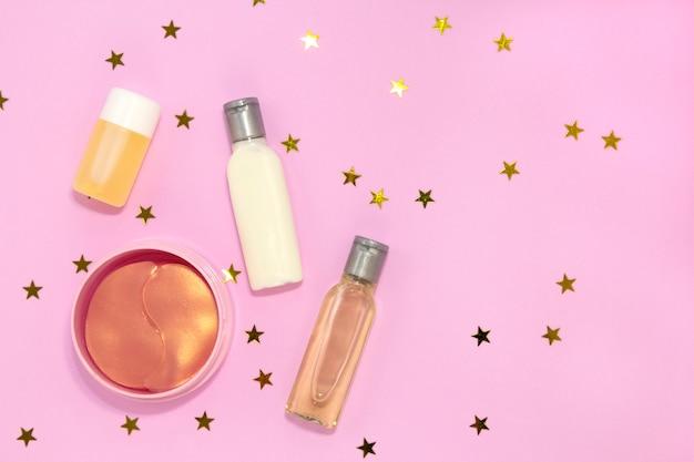 Satz schönheitszubehör für frau, kosmetische augenklappe des hydrogels, glascreme, flaschengel für hautpflege an mit goldenen sternen.