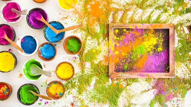 Satz schüsseln mit hellen trockenen farben nähern sich fotorahmen und stapel von farben