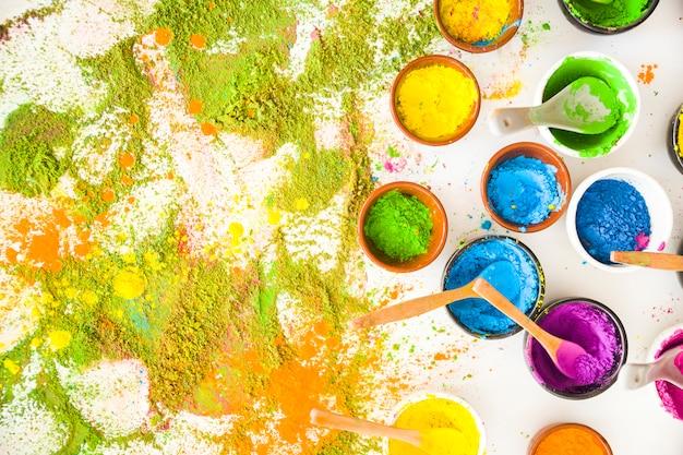 Satz schüsseln mit hellen trockenen farben nahe haufen von farben