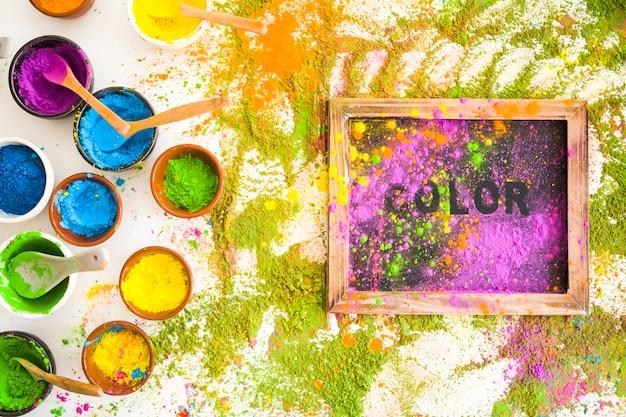 Satz schüsseln mit hellen trockenen farben nahe rahmen mit titel und stapel von farben