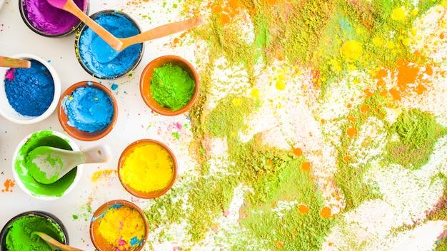 Satz schüsseln mit hellen trockenen farben nahe stapel von farben