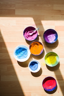 Satz schüsseln mit verschiedenen hellen trockenen farben auf fußboden