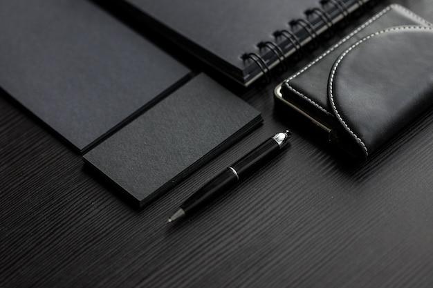 Satz schwarze modelle auf der dunklen, weiblichen hand, die eine visitenkarte hält