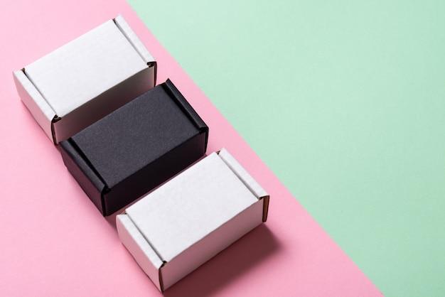 Satz schwarzweiss-kartonschachteln auf grünem und rosa tisch, draufsicht, kopienraum