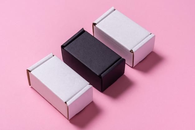 Satz schwarzweiss-kartonschachteln auf rosa tisch, draufsicht, flache lage