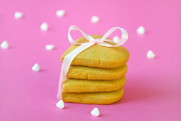 Satz shortbread-kekse gebunden mit rosa band und vielen weißen herzbonbon-konfetti auf pastellrosa