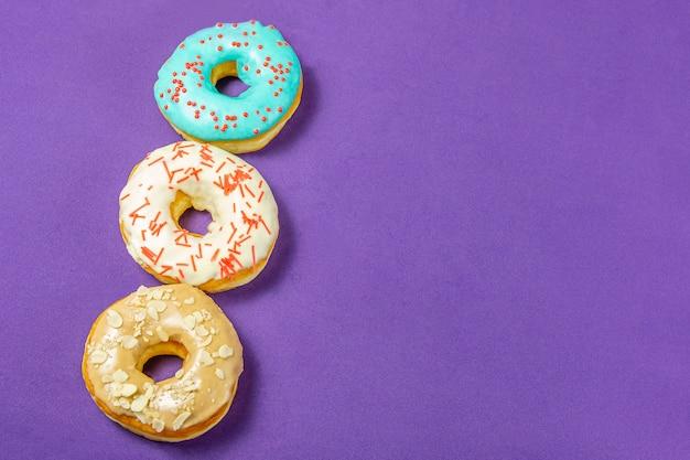 Satz sortierte schaumgummiringe mit blauer glasur, besprühen nahaufnahme auf einer purpurroten tabelle. konzept der süßen nahrung (nachtisch).