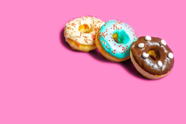 Satz sortierte schaumgummiringe mit der blauen glasur-, besprühen-, schokoladen- und eibischnahaufnahme lokalisiert auf einer rosa tabelle. konzept der süßen nahrung (nachtisch).