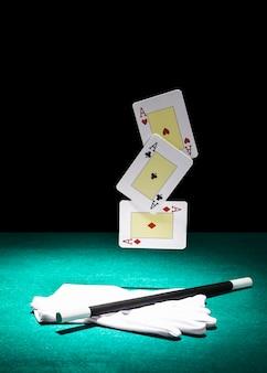 Satz spielkarten der asse über dem paar weißer handschuhe mit magischem stab