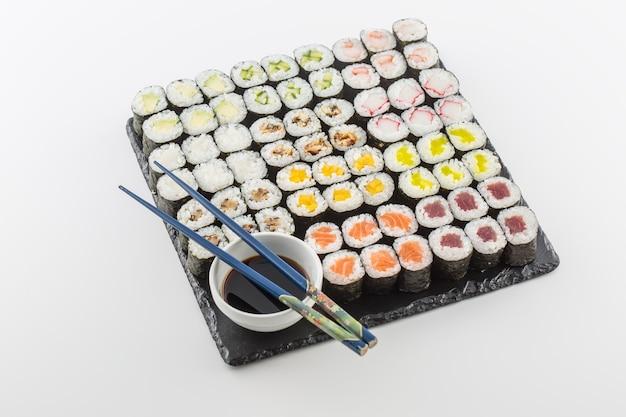 Satz sushi maki auf schieferbrett mit sojasauce und stäbchen, isoliert auf weiss.