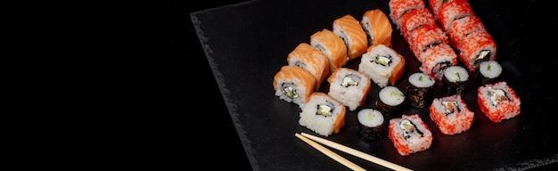 Satz sushi-rolle auf schwarzem schiefer oberflächenfutter fisch philadelphia japanischer lachs köstliche sushi-reis-gurken-mahlzeit traditionelle wasabi frische gesunde gourmet-rohküche