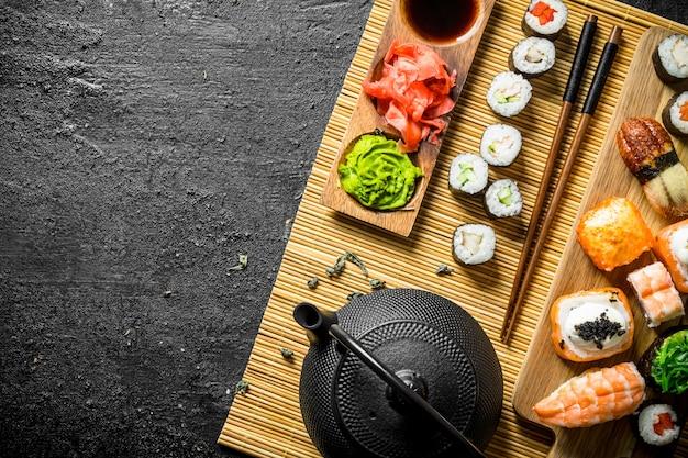 Satz sushi-rollen auf einer serviette mit grünem tee. auf schwarzem rustikalem hintergrund