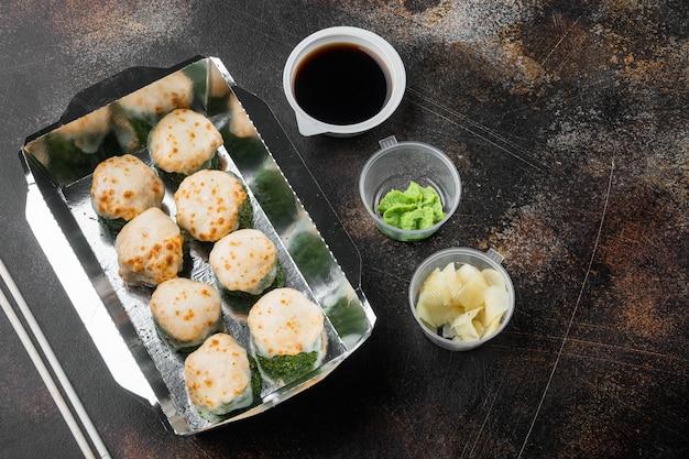 Satz sushi-rollen in lieferbox-set, auf altem dunklem rustikalem tisch