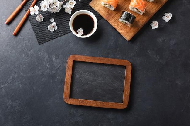 Satz sushi- und maki-rollen mit zweig aus weißen blumen und kreidetafel auf steintisch. draufsicht mit platz für ihren text.