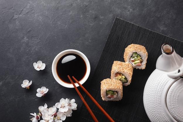 Satz sushi- und maki-rollen mit zweig aus weißen blumen und teekanne auf steintisch. ansicht von oben.