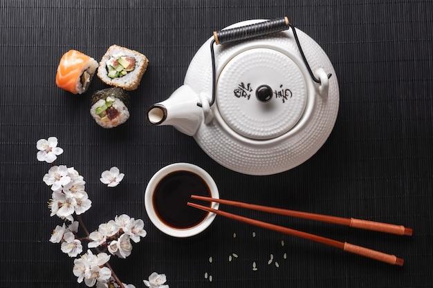 Satz sushi- und maki-rollen mit zweig aus weißen blumen und teekanne mit der aufschrift grüner tee auf steintisch. ansicht von oben.