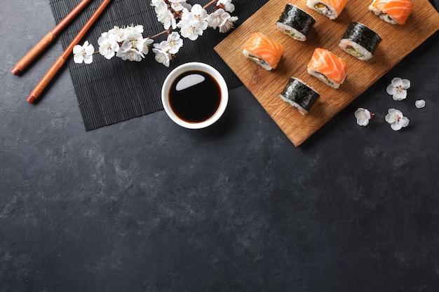 Satz sushi- und maki-rollen mit zweig weißer blumen auf steintisch. ansicht von oben.