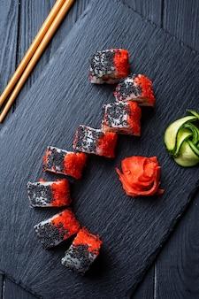 Satz sushirollen mit frischkäse, reis und lachs auf einem schwarzen brett, verziert mit ingwer und wassabi auf einem dunklen holztisch. japanische küche. lebensmittelfototisch. draufsicht