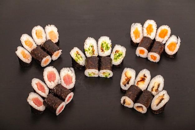 Satz sushirollenlebensmittel auf schwarzem