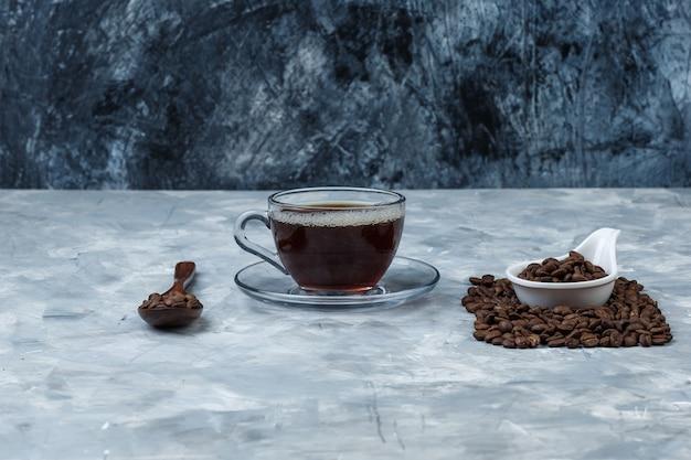 Satz tasse kaffee und kaffeebohnen in einem holzlöffel und einem weißen porzellankrug