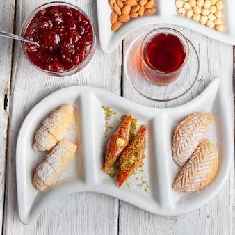 Satz tee, nüsse, fruchtmarmelade und köstliche desserts auf einem weißen hölzernen hintergrund. draufsicht.