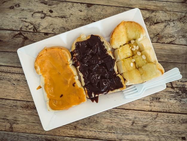 Satz toastbrote mit unterschiedlichem belag von erdnussbutter, schokolade und butter.