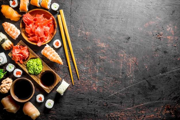 Satz traditionelles japanisches sushi und brötchen mit mariniertem ingwer und sojasauce auf rustikalem tisch