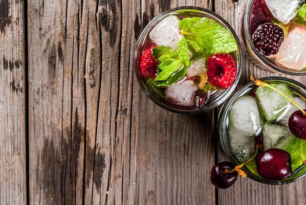 Satz traditionelles sommerauffrischungsgetränkbeere mojito. mit limette, minze, brombeeren, himbeeren und kirschen. mit den zutaten auf alten rustikalen hölzernen steintisch. ansicht von oben