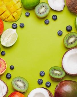 Satz tropische früchte kiwi, blutorange, kokosnuss, mango, blaubeere, limette, auf grüner wand. fropical fruit food frame. flatlay mit copyspace. immunitätskonzept. früchte zur stärkung der immunität. pop