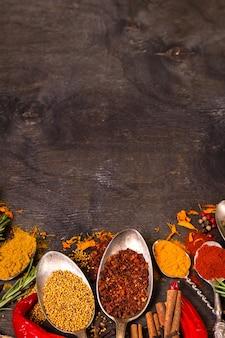 Satz verschiedene aromatische bunte gewürze in alten weinlöffel und kräutern auf einem dunklen hölzernen hintergrund.