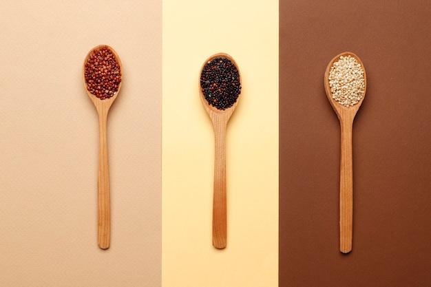 Satz verschiedene arten von quinoa in holzlöffeln auf braunem hintergrund