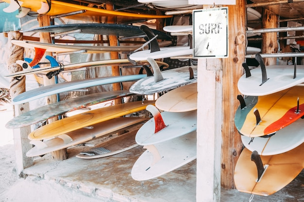 Satz verschiedene bunte surfbretter in einem stapel vorhanden für miete am strand. vintage farbtoneffekt.