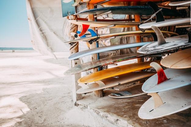 Satz verschiedene bunte surfbretter in einem stapel vorhanden für miete am strand.